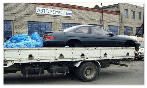 автомобиль без колёс везут в ремонт.